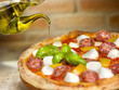 Italian pizza with tomato, mozzarella, peppers salami and basil
