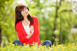 Happy woman with headphones relaxing in the park