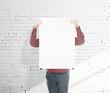 man holding blank poster