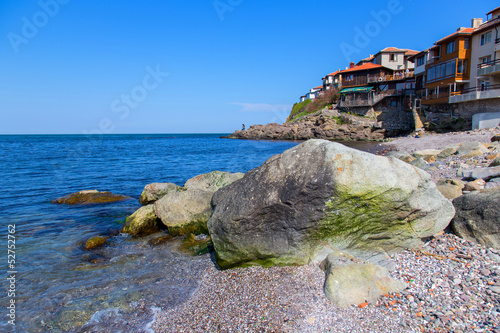Seascape old town with rocks in the foreground