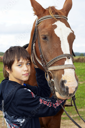 Young boy pets a horse after a walk Poster