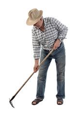 a farmer works with a garden tool