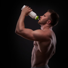 Muscular guy drinking water after training