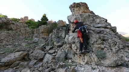 climber climbing the top of the rock