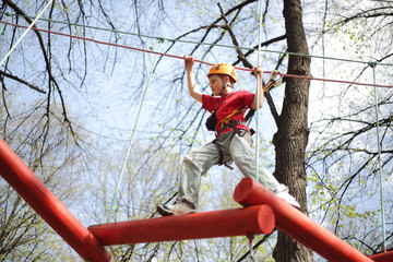 climber skilfully go on suspension bridge in high ropes course.