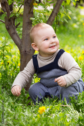 A little boy sitting on the grass and smiling.