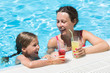 Mother and daughter swimming in pool with drink in hand