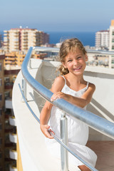 A girl stands on the balcony of hotel on background of cityscape