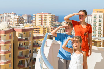 Family on balcony of room at hotel looking into distance