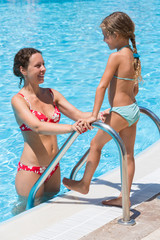 The girl goes to the pool to swim with mother.