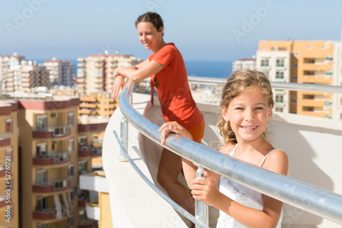Mother and daughter on balcony of room at hotel