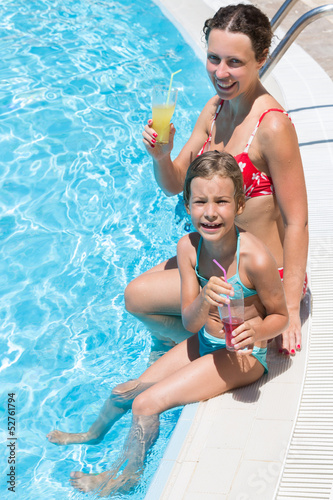 mother and daughter sitting on edge of pool with drink