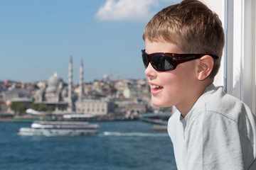 Boy in sunglasses against landscape with river and mosque