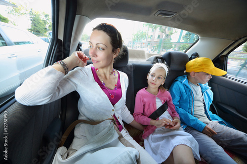 Mother, daughter and son in the back seat of a car