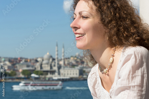 Beautiful woman in landscape with river and mosque