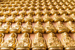 Many of small golden Buddha statue on the wall