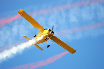 airplane with smoke in blue sky