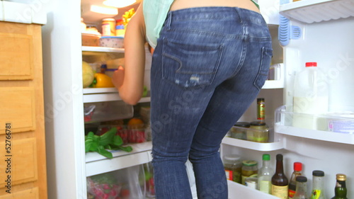 Behind of Mexican woman searching refrigerator