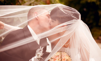 Wedding couple kissing covered veil