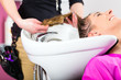 Woman at the hairdresser washing hair
