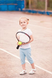 Adorable little child playing tennis