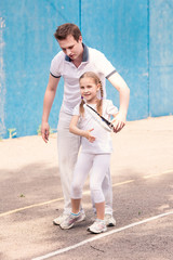 Instructor teaching a child how to play tennis