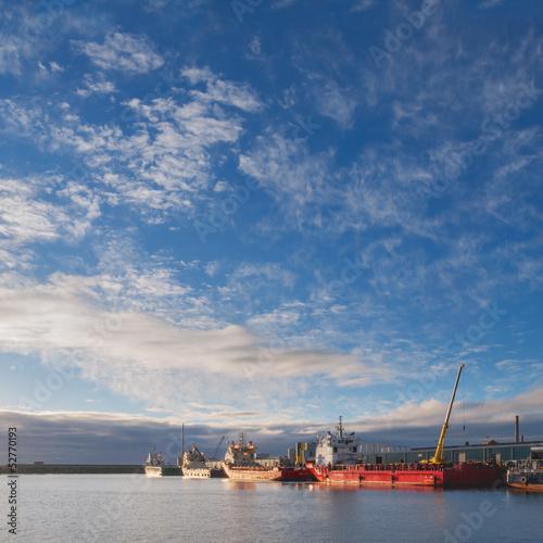 Oil platform supply vessels in a port during sunrise
