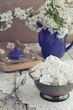 Still life in vintage style with meringue kisses and cherry flow