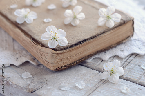 Cherry flowers laying upon old book on lace doily