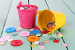 Colorful buttons strewn from buckets on wooden background