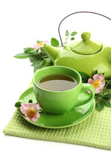 Cup and teapot of herbal tea with hip rose flowers, isolated