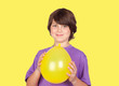 Adorable preteen boy with a yellow balloon