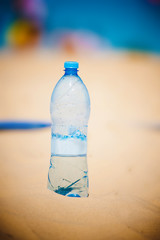 bottle of water standing in sand at the beach