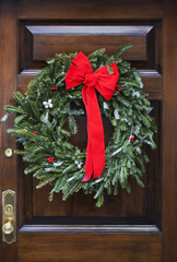 Wooden front door decorated with writh and red bow.