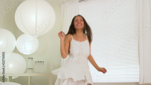 Mexican woman dancing in white dress in bed room
