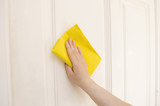 hand cleaning a door white with a yellow cloth