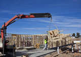 Workman guides load of trusses for housing under construction
