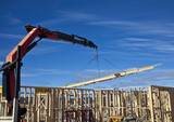 Crane lifts trusses onto new houses under construction