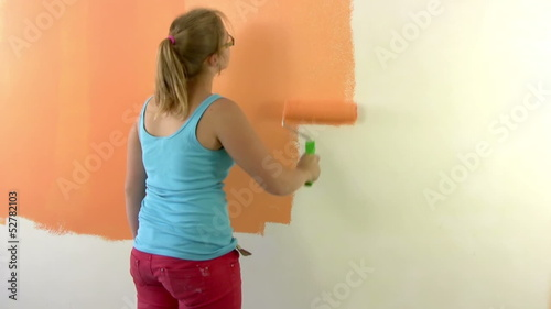 Girl teenager paints a wall in orange