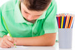 Little boy drawing with colorful pencils, isolated over white