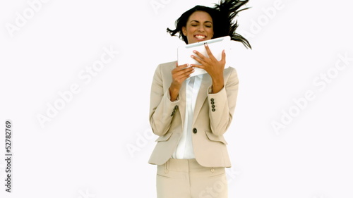 Businesswoman jumping and holding tablet