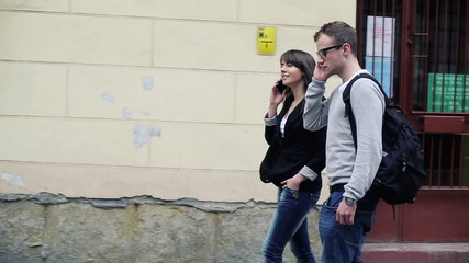 Students walking and talking on cellphone in the city
