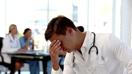 Young worried doctor holding his head