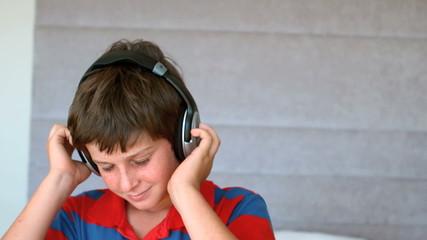 Dancing young boy enjoying music with headphones