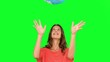 Woman throwing a globe in the air on green screen