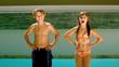 Siblings dancing and diving into the swimming pool