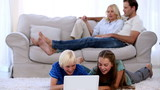 Parents relaxing on couch with children using laptop