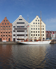 Sailing vessel and old town houses over Motlawa river in Gdansk,