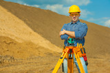 worker with theodolite on construction site