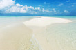 Seascape with white sand on the beach and blue sky with clouds